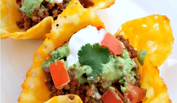 Square image of cheesy keto taco shells filled with ground beef, tomatoes, guacamole, sour cream and cilantro on a white plate with a green and white tablecloth under it.