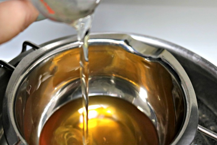 Oils being added to beeswax in a double boiler