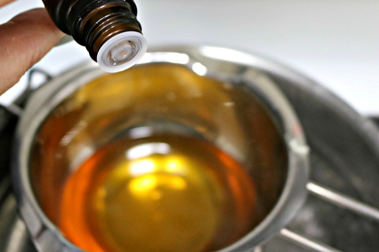 Essential oils being added to a double boiler of beeswax and oil.