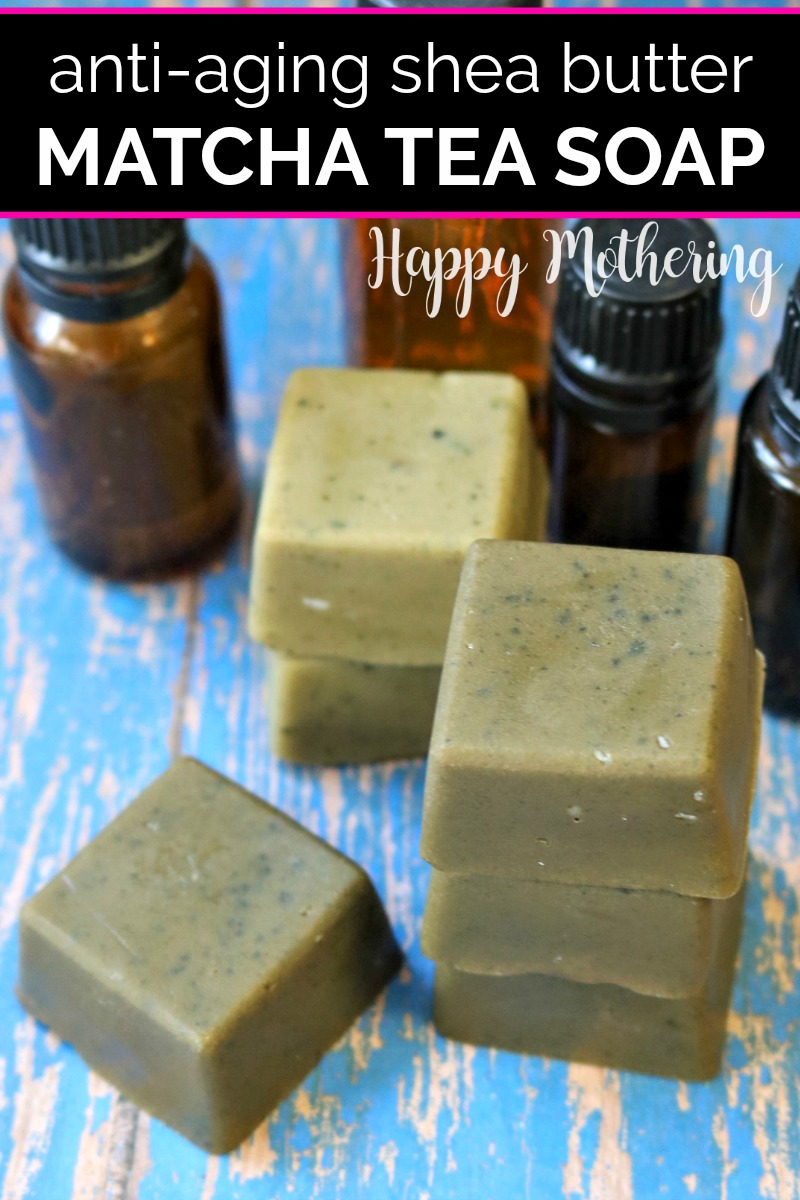 Matcha green tea soap bars on a blue wood table next to essential oil bottles