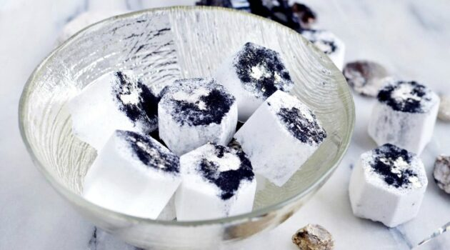 Clear decorative glass bowl on a marble counter filled with charcoal bath bombs with more spilling onto the counter