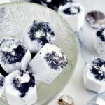 Some charcoal bath bombs in a clear glass bowl with more scattered on the white marble counter with crystals