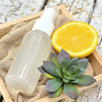 Bottle of homemade bug spray in a wood crate with lemon and and a succulent