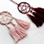 Two dreamcatcher necklaces on a white table