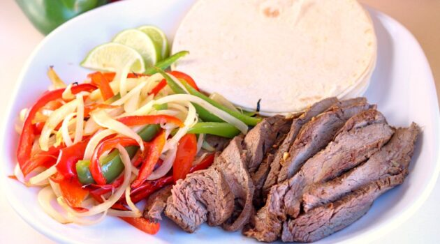 Steak, bell peppers and onions with sour cream on a white dinner plate