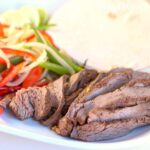 Instant Pot Steak Fajitas with flour tortillas, bell peppers and onions