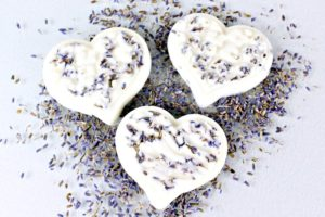 Three homemade lavender lotion bars shaped like hearts on dried lavender buds on a white wood table
