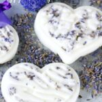 Homemade lavender lotion bars on top of lavender petals on a table