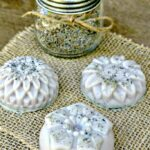 Three homemade shampoo bars on burlap with a jar of lavender petals
