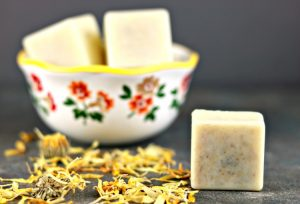 Calendula lotion bar on a counter next to a bowl filled with more