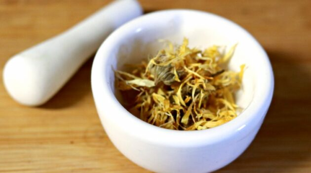 Calendula flower petals in a mortar with pestle