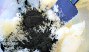 Adding charcoal powder to bowl with salt and oils