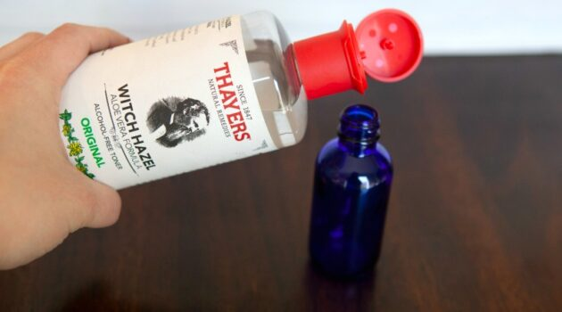 Adding witch hazel to the essential oils in a blue glass spray bottle