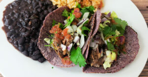 Barbacoa beef served in blue corn tortillas, topped with salsa, cilantro and onion and served with with black beans and Spanish rice.