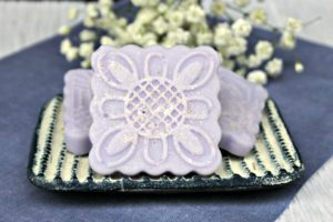 Lavender salt scrub bars on a blue and white soap dish on a blue placemat with white flowers