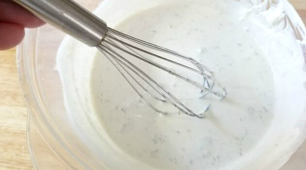 Homemade sunscreen ingredients in a mixing bowl with whisk