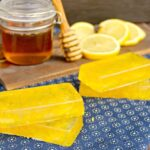 4 Honey Lemon Soap Bars on a blue napkin next to a cutting board, jar of honey and slices of lemon on a brown wood table.