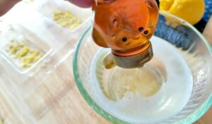 Pouring honey into the melted glycerin soap mixture with the soap mold lined with lemon zest behind it.