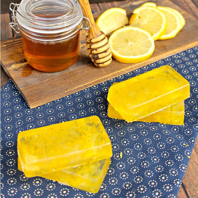 4 homemade honey lemon soap bars on a blue cloth with a white pattern on it. Behind the soap bars are a jar of honey and sliced lemon on a cutting board.