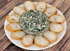 Spinach dip in a glass bowl in the center of a white plate surrounded by bread slices on a wood table