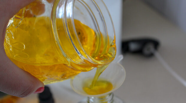Olive oil, white vinegar, castile soap and essential oil mixture being poured through a funnel into a spray bottle