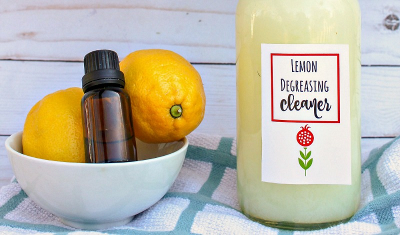 Close up of degreasing cleaner sat next to a bowl of lemons with a bottle of essential oil in it