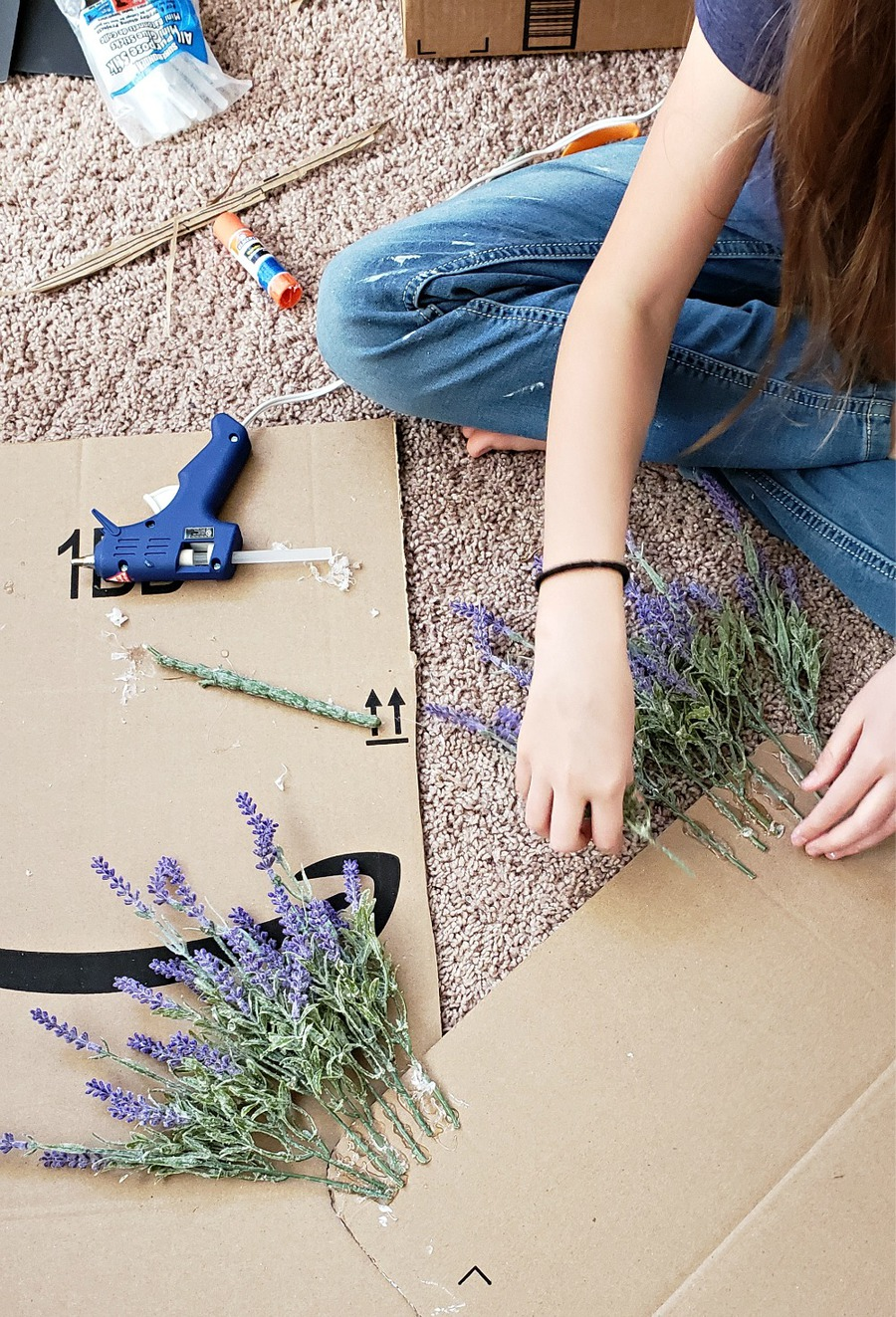 Hot gluing lavender flowers onto the back of the cardboard cutout.
