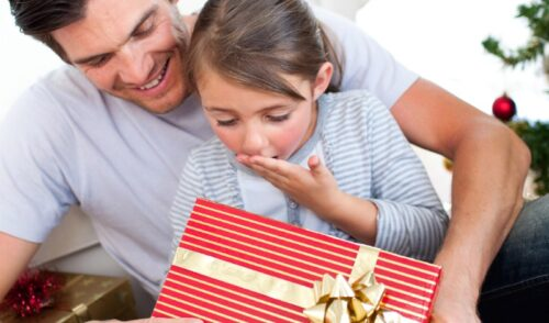 Little girl and her dad opening a present