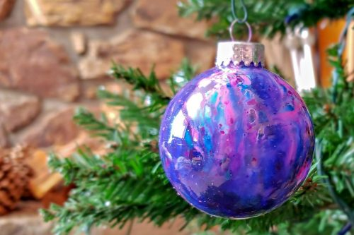 Melted crayon galaxy ornament hanging on a Christmas tree in front of the fireplace