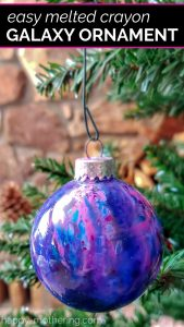 Purple, pink and blue melted crayon globe ornament that looks like a galaxy