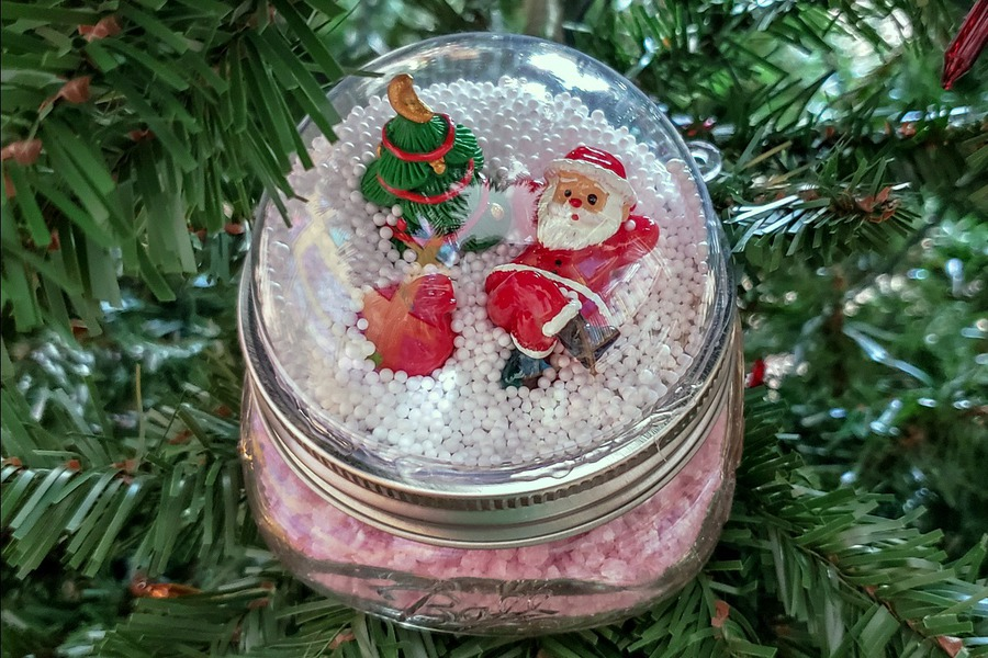 Santa Mason Jar Snow Globe Topper on a Christmas tree branch