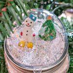Snowman Snow Globe Mason Jar Lid Topper on a Christmas tree branch