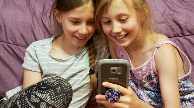 Zoe and Kaylee looking at a cell phone at a funny video