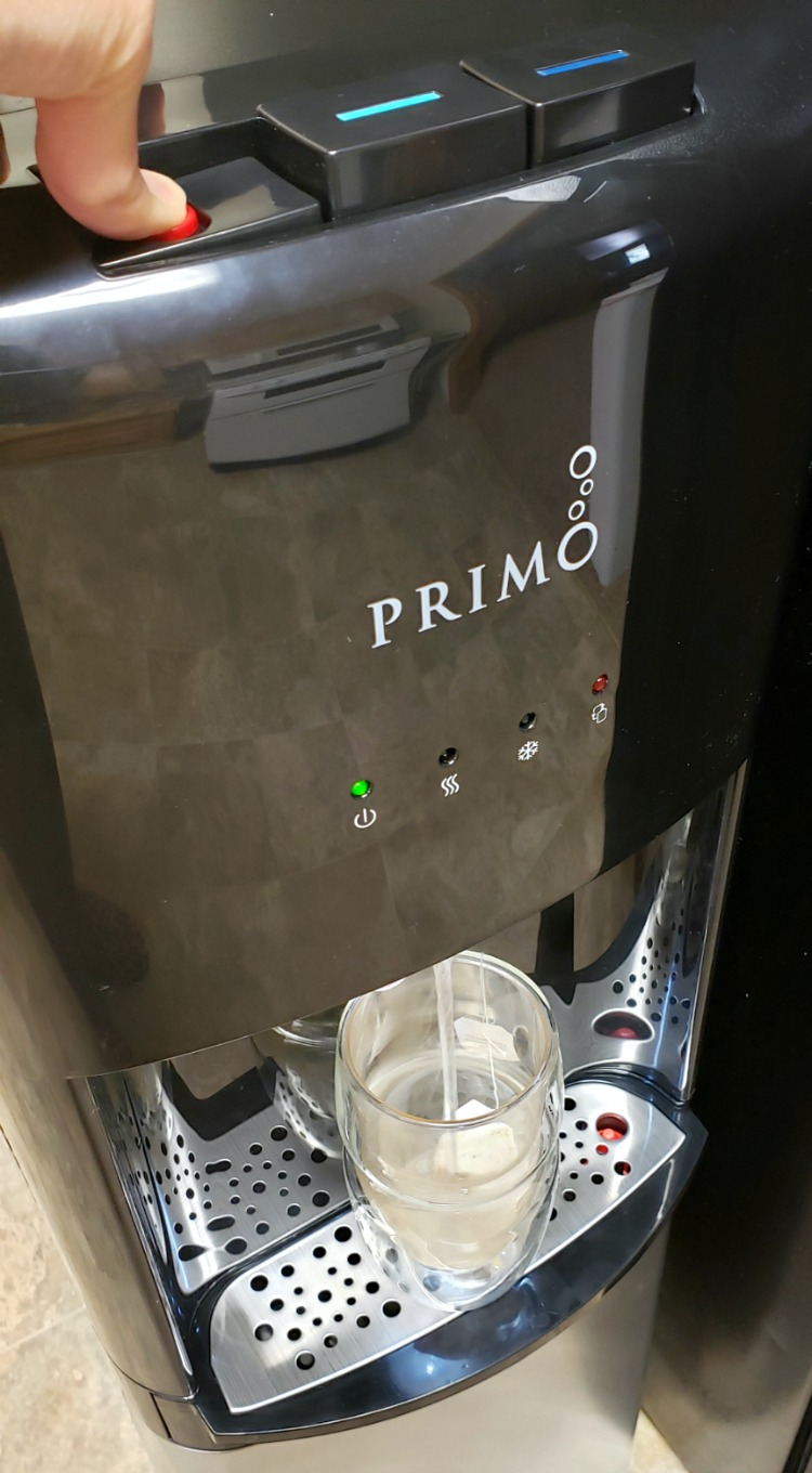 Primo water dispenser dispensing hot water into a clear glass cup over a tea bag