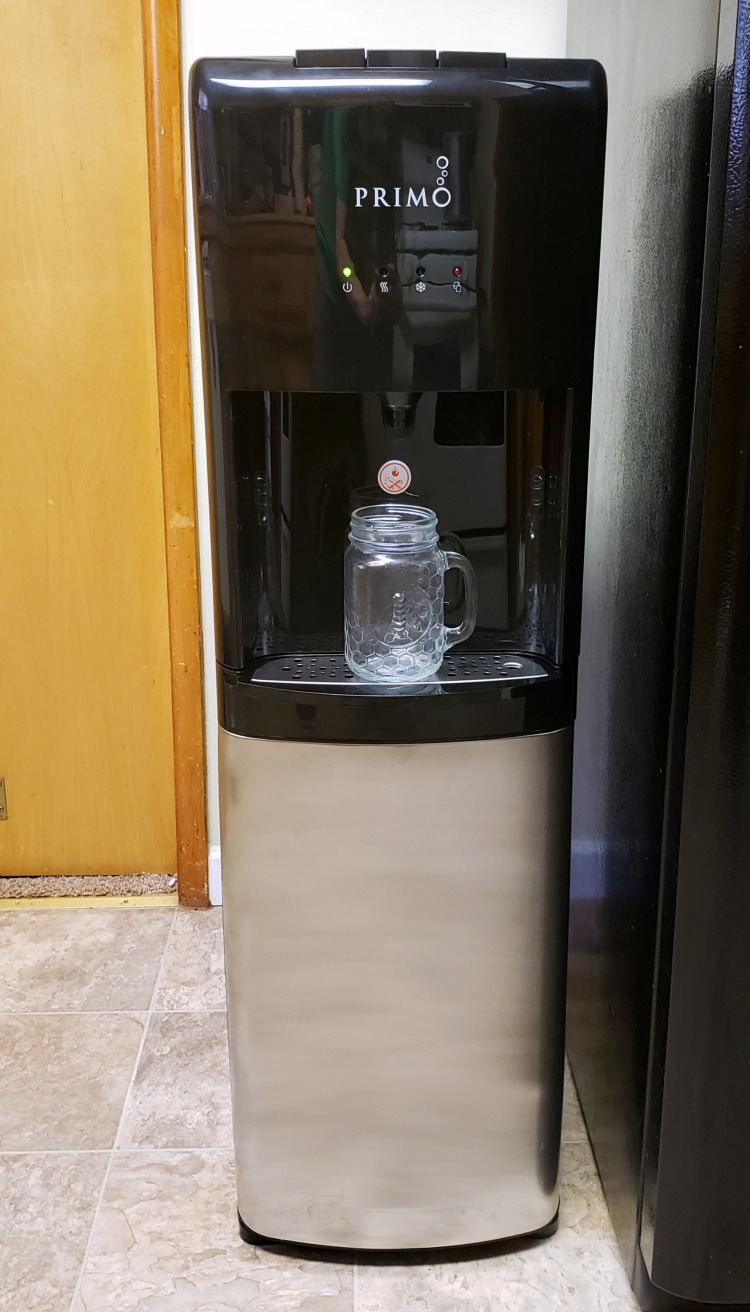 Primo bottom loading water dispenser in a kitchen with a mason jar on the drip tray