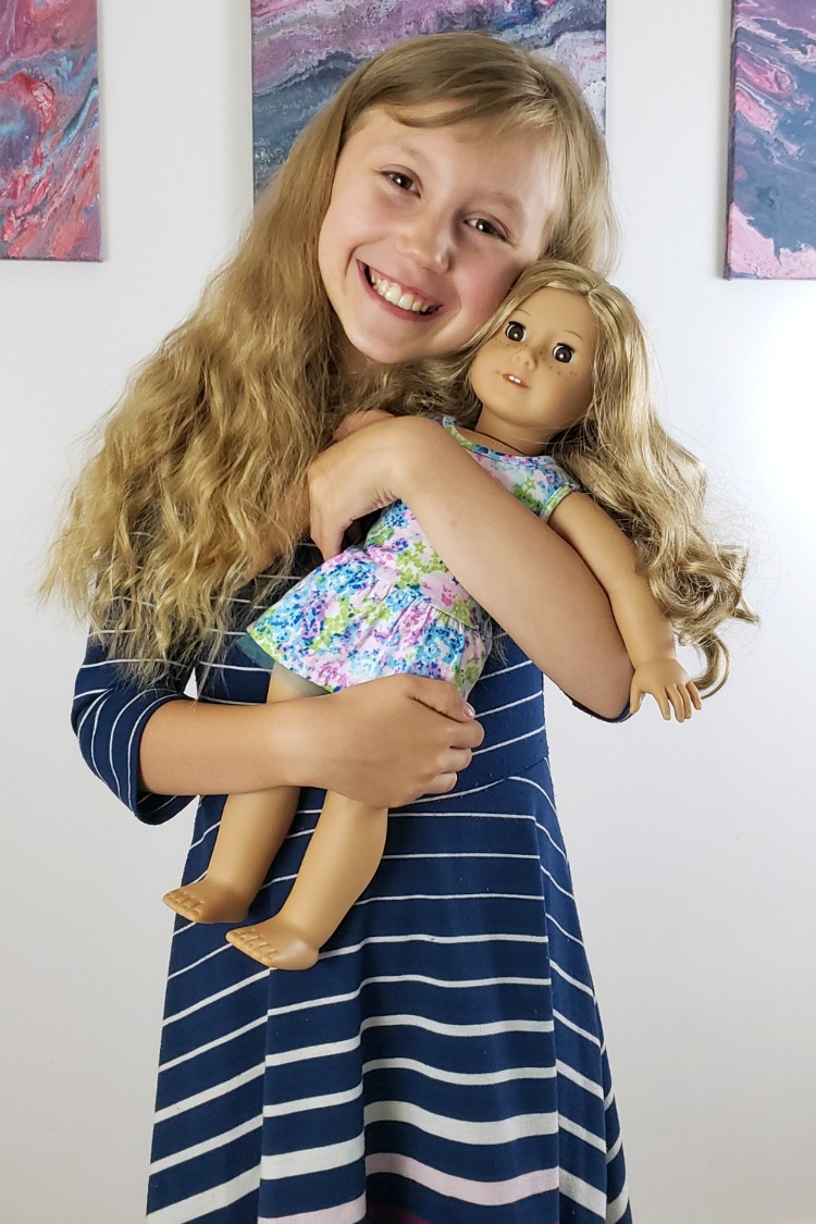 Kaylee hugging her American Girl Truly Me doll Abby with paintings on a white wall in the background