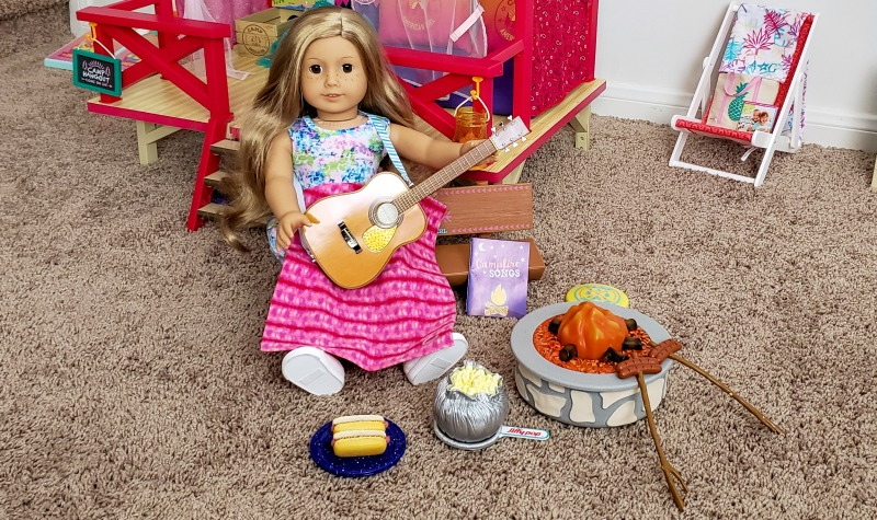Camp American Girl Campfire set in front of the Camp American Girl Hangout with a Truly Me doll with long blond hair sitting on the bench