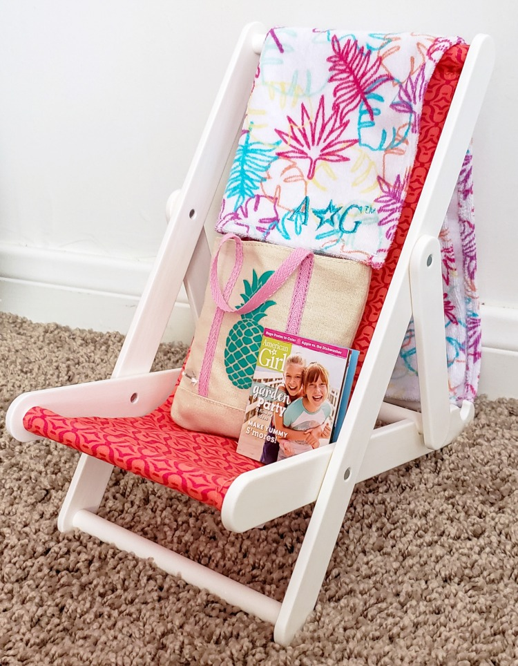 Reclining chair that comes with the American Girl Swimming Pool set with a colorful towel, pineapple bag and American Girl magazine sitting in it.