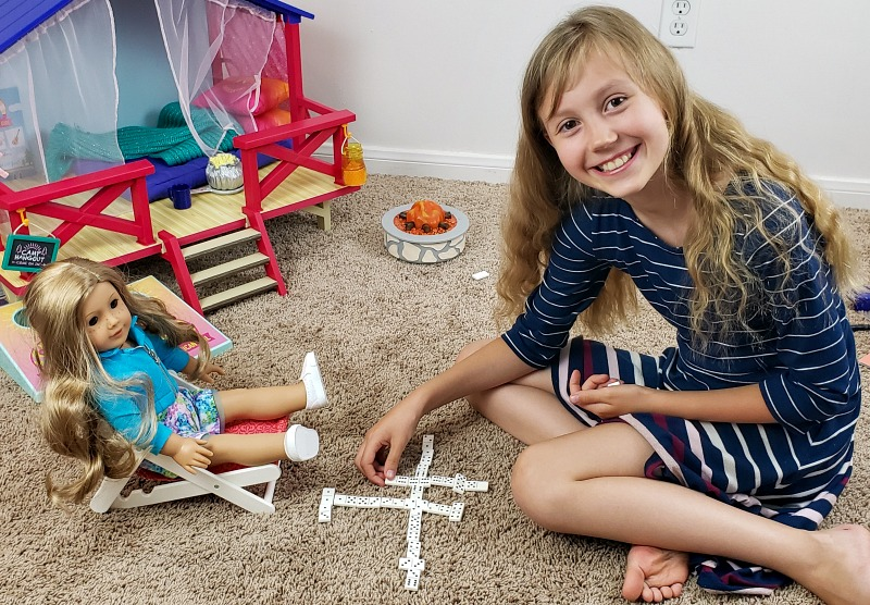 Kaylee and her Truly Me doll Abby playing dominoes in front of the Camp American Girl Hangout