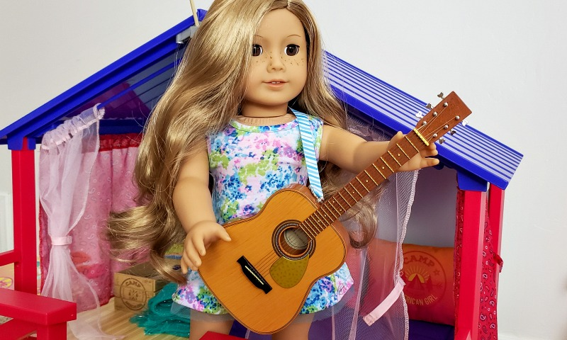 American Girl Truly Me Doll 24 standing in front of the Camp American Girl Hangout holding the guitar from the Campfire Set.