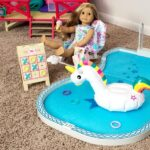 American Girl Swimming Pool set up on carpet with Truly Me doll reclining in the chair next to the game board.