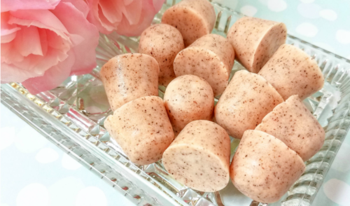 Apricot seed sugar scrub cubes on a clear platter with pink flowers on a light green background with white polka dots.