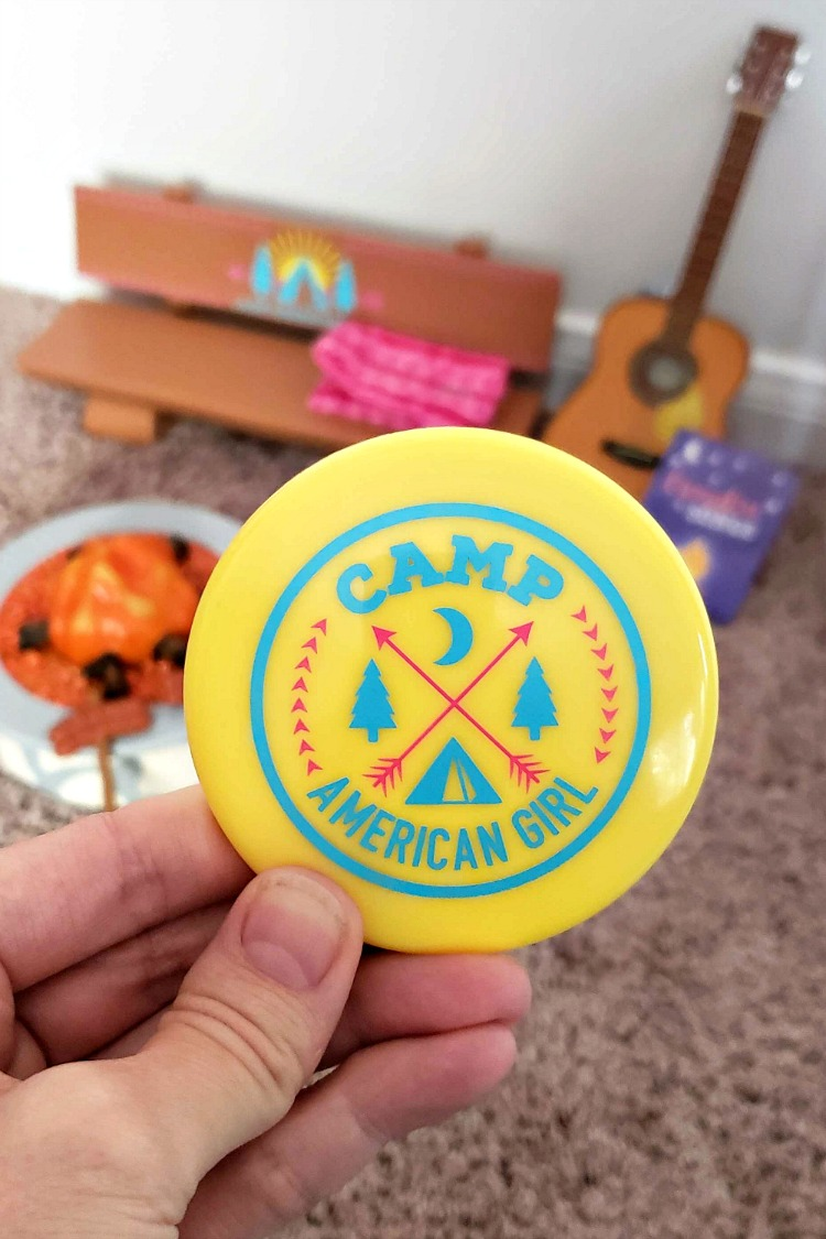 The yellow flying disc that saying Camp American Girl in blue writing with pink arrows from the Camp American Girl Campfire set.