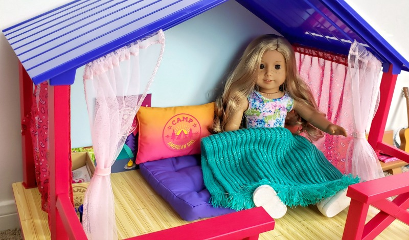 Abby sitting inside of the Camp American Girl Hangout covered up by the teal blanket while sitting on purple cushions against pink and orange ombre pillows.