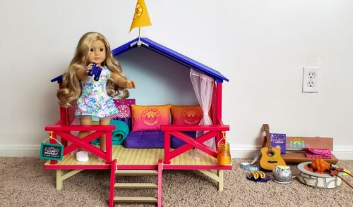 Camp American Girl Hangout with Truly Me doll 24 standing on the porch next to the Campfire set on tan carpet with a white wall background
