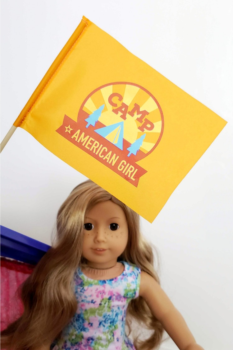 Camp American Girl Hangout flag in front of a Truly Me doll with blond hair and a floral dress.