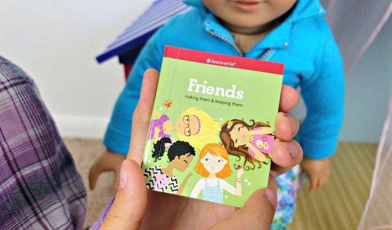 Kaylee holding the miniature Friends book from the Camp American Girl Hangout set.