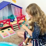 Kaylee playing the Camp American Girl Outdoor Games with her Truly Me Doll Abby while sitting next to the Camp American Girl Hanout on tan carpet