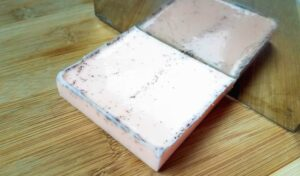 Soap brick on a bamboo cutting board being chopped with a soap cutter