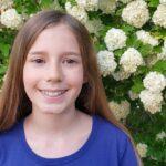 Zoe in front of hydrangea bush